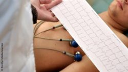 Image: Physician looking at the print-out of an ECG curve next to a patient; Copyright: PantherMedia/voenkor