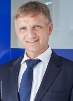 Image: Smiling man with short grey hair, blue tie and blue suit - Armin Schorer; Copyright: ASANUS Medizintechnik GmbH