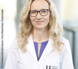 Image: A smiling physician with long blond hair, glasses and a white coat; Copyright: Universitätsklinikum Ulm/Matthias Schmiedel