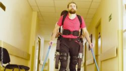 Image: A young man walks along a hospital hallway using crutches and an exoskeleton; Copyright: PantherMedia/chudakov