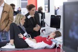Image: young woman on couch, exhibitor shows ultrasound device; Copyright: Messe Düsseldorf