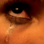 Photo: The eye of a woman crying, with a tear running down