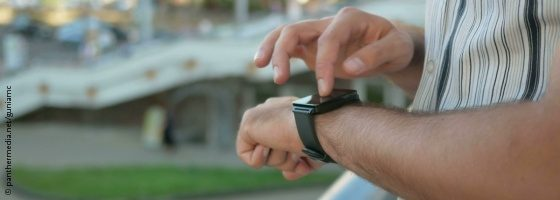 Image: A man is standing outdoors while typing on his smart watch; Copyright: panthermedia.net/guniamc""