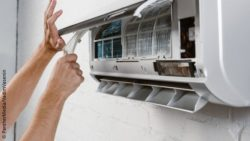 Image: A man is opening and repairing a wall-mounted air condition device; Copyright: PantherMedia/VadimVasenin
