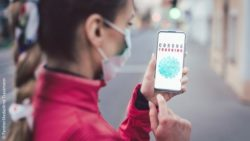 Image: woman with face mask holding a smartphone with the corona tracking app; Copyright: PantherMedia/Arne Trautmann